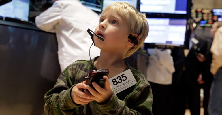 Jordan Kessler, the 5-year-old son of trader Glenn Kessler, uses his father's mobile phone and badge as he visits the floor of the floor of the New York Stock Exchange, Friday, Nov. 28, 2014. U.S. stocks are ending mostly lower as falling crude prices weigh on the market in a holiday-shortened session. Children traditionally accompany parents and relatives on the floor during the shortened trading day after Thanksgiving. (AP Photo/Richard Drew)