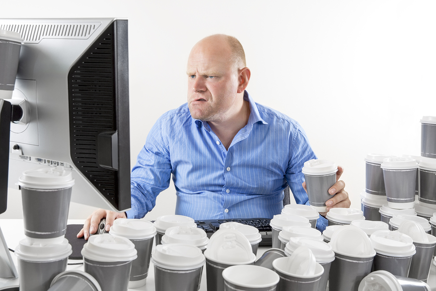 Overworked and exhausted office worker drinks too much coffee.